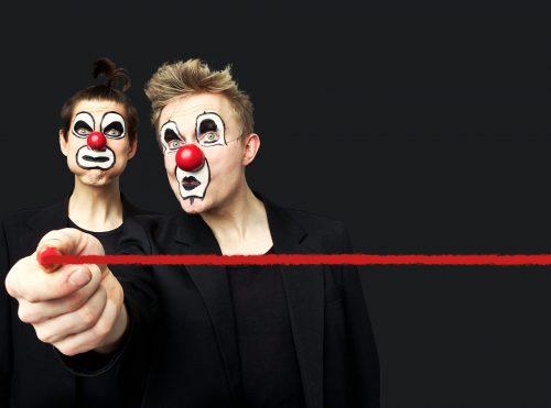 Klovnineniin ja tummiin pukuihin sonnustautuneet miehet poseeraavat hassutellen kameralle. Toinen vetää kynällä kuvan poikki punaisen vaakaviivan.