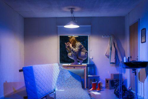 Klara Harmaa (Minni Gråhn) kyykyssä pöydällä. Asunto on sotkuinen, sänky on kaadettu kyljelleen ja patja on lattialla.