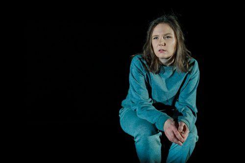 Klara Harmaa (Minni Gråhn) jakkaralla, tähyilee kaukaisuuteen. Tausta on pimeä.