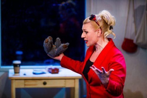 Ursula Harmaa (Regina Launivuo) puhuu Klaran asunnossa kädet levällään, toisessa kädessä nallekarhu.