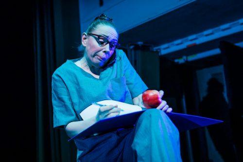 Natsku (Suvi-Maaria Virta) puhuu puhelimeen, kirjoittaa kansioon muistiinpanoja ja syö samalla omenaa.