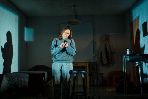 Klara Harmaa (Minni Gråhn) näppäilee puhelinta hämärässä asunnossa.