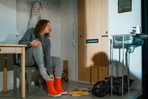 Klara Harmaa (Minni Gråhn) laittaa punaisia kumisaappaita jalkaan asunnossaan. Lavuaarin alla on täysiä roskapusseja.