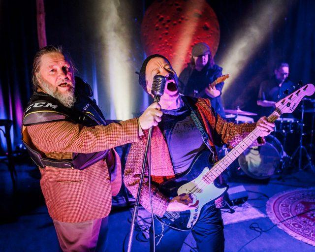 Olli-Kalle Heimo ojentaa mikkiä kitaraa soittavalle Jaakko Tohkaselle. Bändi soittaa takana.