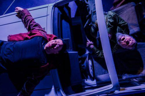 Jaakko Tohkanen ja Olli-Kalle Heimo makaavat auton konepellillä ja penkeillä ja katselevat ylöspäin suoraan kameraan.
