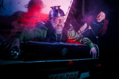 Olli-Kalle Heimo istuu auton konetilassa pastasiivilä päässään. Jaakko Tohkanen yrittää vetää häntä köydestä ylös.