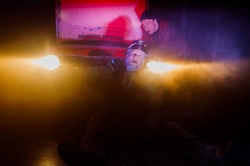 Olli-Kalle Heimo istuu auton edessä auton valokeilojen loisteessa pastasiivilä päässään.