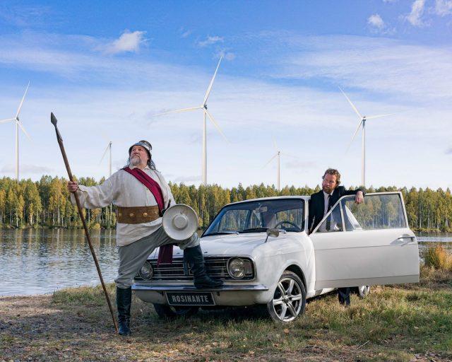 Olli-Kalle Heimo on pukeutunut ritarilliseen asuun ja poseeraa keihäs kädessään vanhan auton vieressä. Jaakko Tohkanen katsoo ihmeissään puku päällä. Jokimaisemassa tuulivoimaloita.