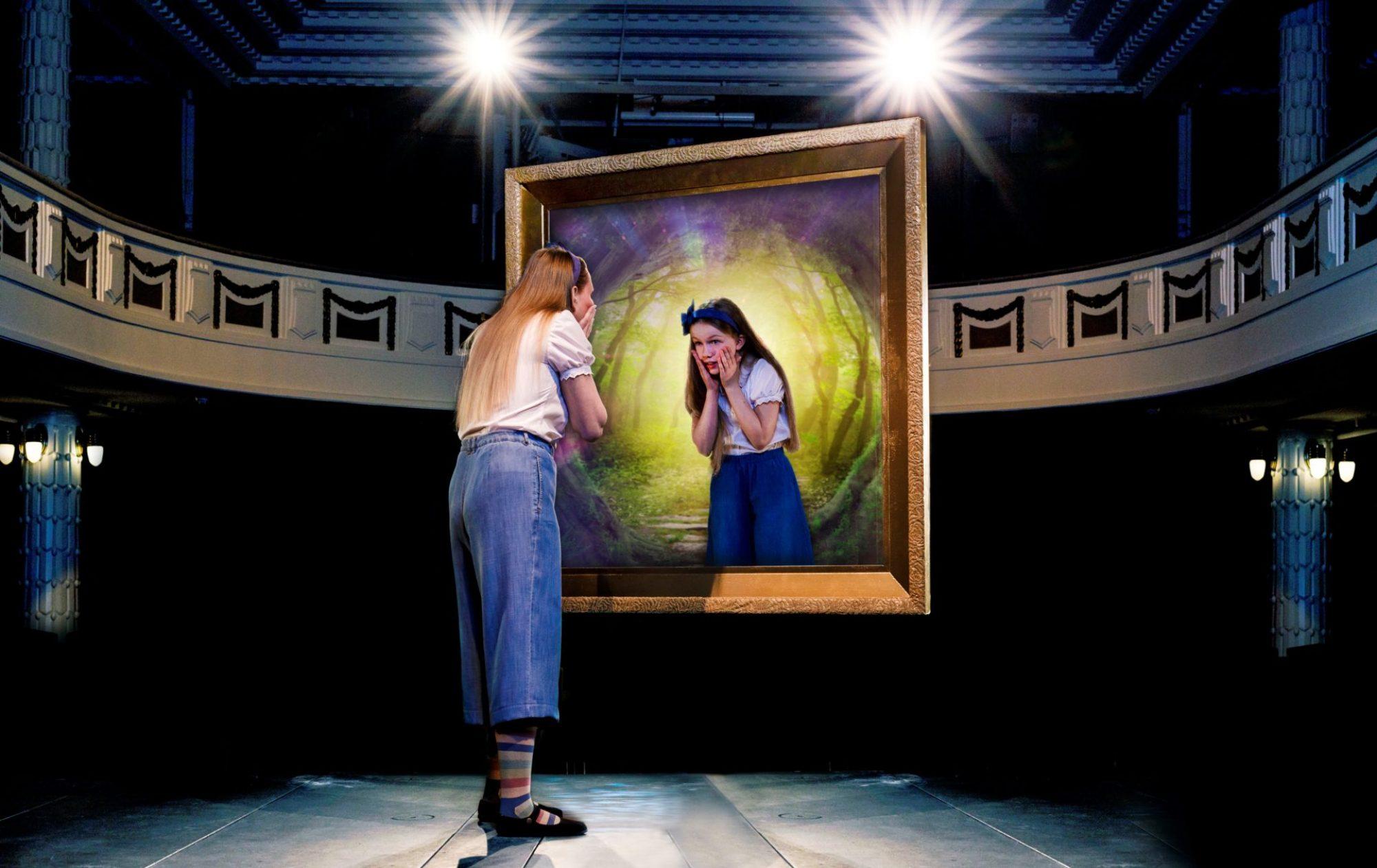 Liisa (Suvi-Maaria Virta) katsoo peiliin teatterin suurella näyttämöllä. Peilistä häntä katsoo identtinen pikku-Liisa.