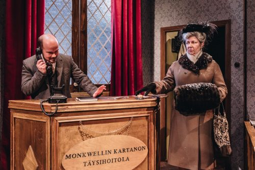 Rouva Boyle vastaanottotiskin ääressä, Giles Ralston puhuu puhelimessa