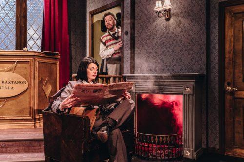 Neiti Casewell lukee lehteä takan ääressä, Christopher Wren kurkistaa taustalta