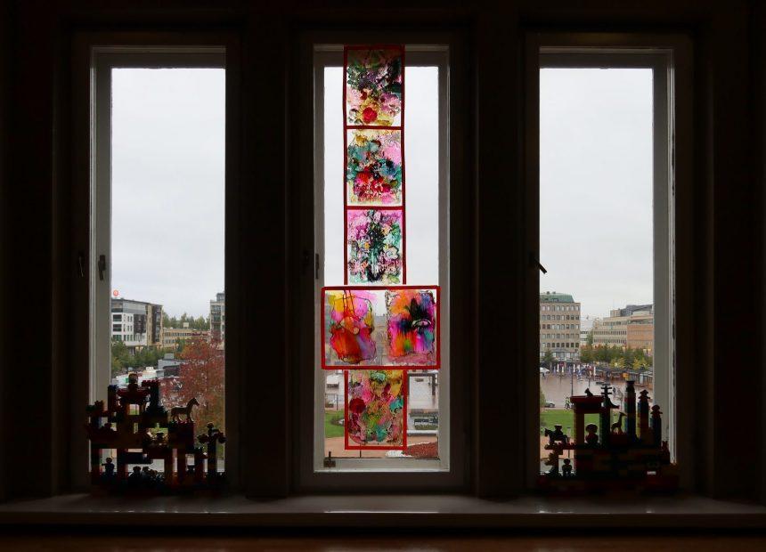 Kapeiden korkeiden ikkunoiden eteen on aseteltu kaksi pienempää rakennelmaa ja keskimmäiseen ikkunaan läpikuultavia, värikkäitä teoksia. Taustalla näkyy Joensuun keskustaa.
