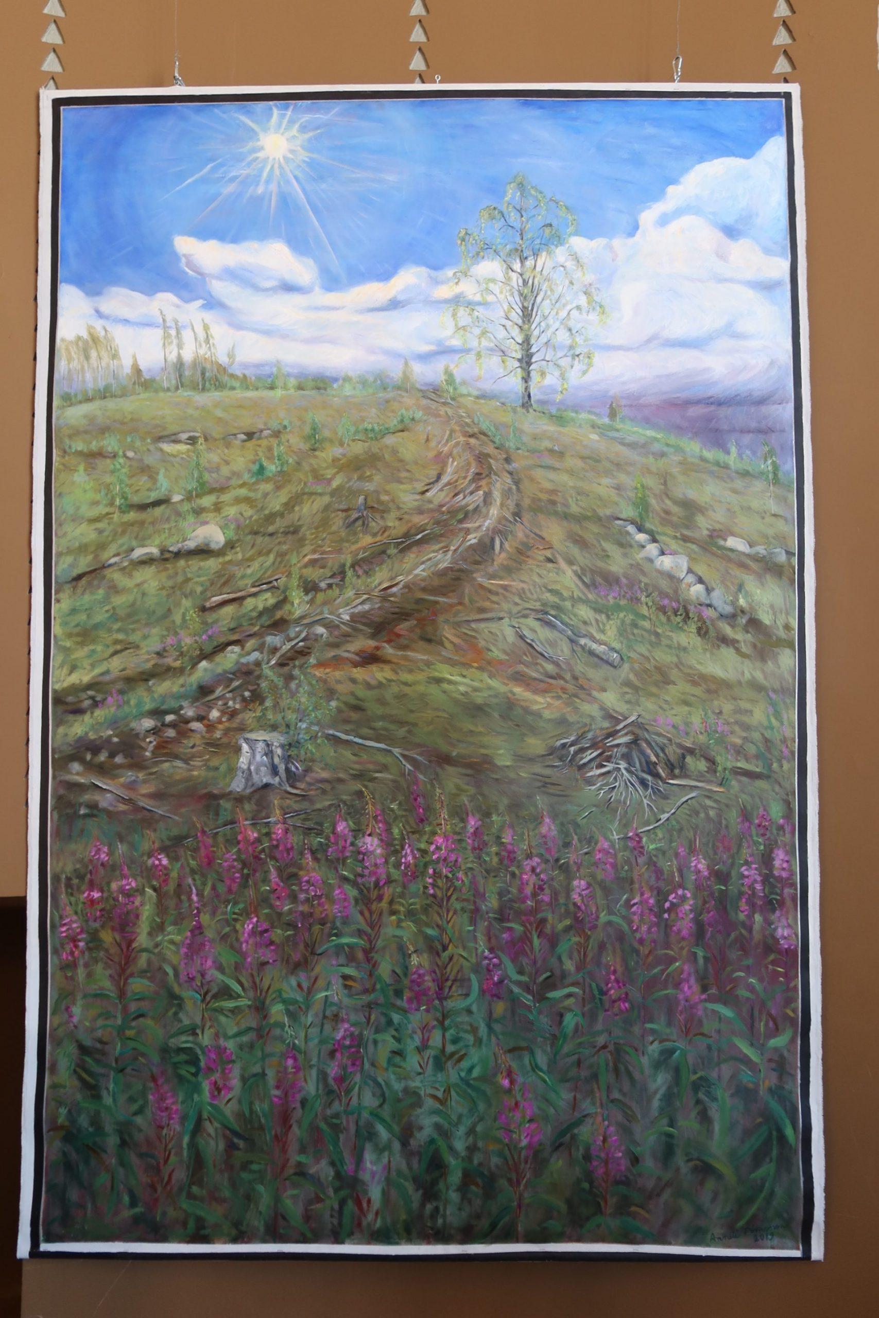 Maalauksessa on koivu mäen päällä, Aurinko paistaa ja mäellä kasvaa kukkia.