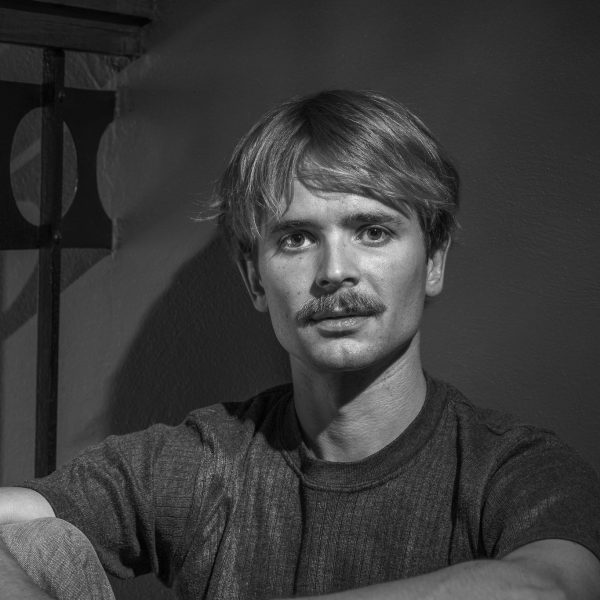 Näyttelijä Hannes Mikkelsson harmaasävyisessä valokuvassa. Hän istuu seinään nojaten metallisen kaiteen vieressä sisätiloissa. Hanneksella on viikset ja otsan peittävä tukka, joka on korvallisilta lyhyempi. Päällä on rento lyhythihainen yksivärinen t-paita. Hannes istuu polvet koukussa ja pitää käsivarsiaan polvien ympärillä, toinen käsi pitelee toisesta ranteesta kevyesti kiinni.