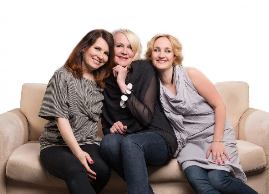 Kolme naista istuu sohvalla ja poseeraa hymyillen kameralle toisiaan kohti likistyen.