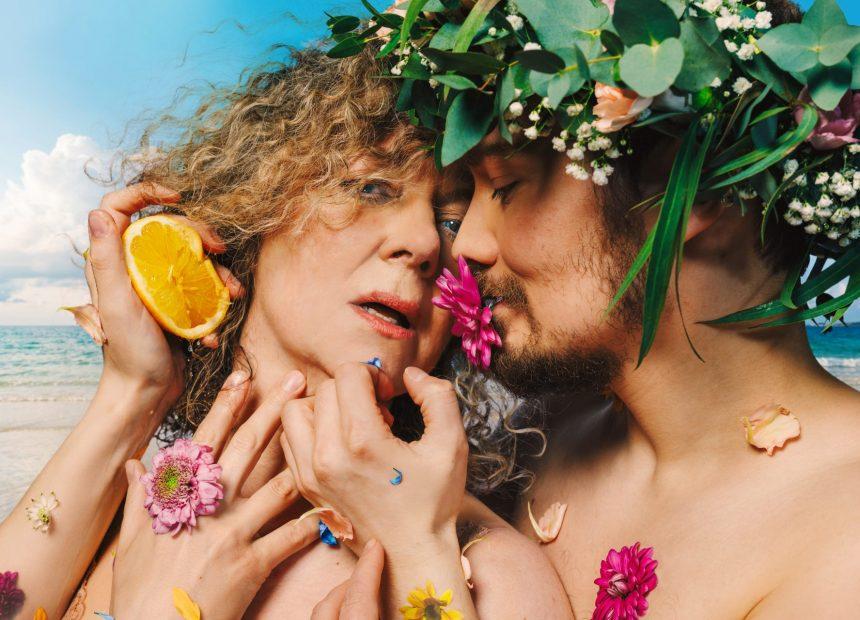 Vanhempi nainen ja nuorempi mies lähikuvassa. Kasvot ja kädet koskettavat toisiaan. Miehen päässä on kukkaseppele ja kummankin iholla on värikkäitä kukkasia. Kuvassa näkyy molempien paljaat hartiat. Taustalla pilkahtaa turkoosi meri ja sininen taivas.