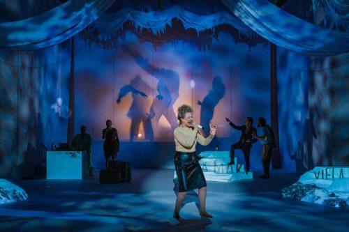 Nainen laulaa. Tausta on hämärä ja takaseinään heijastuu liikkuvien hahmojen varjoja.