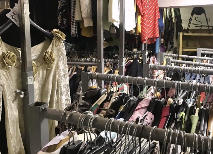 Paljon vaatteita roikkuu henkareilla vaateräkeissä.