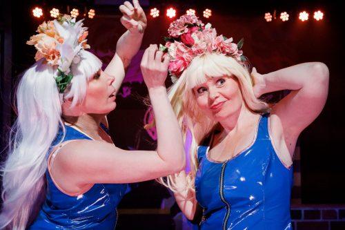 Suvi-Maaria Virta ja Maria Karhapää sinisissä mekoissa ja kukkaseppeleissä