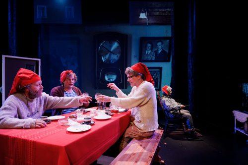 Alma Hurskainen (Olli Haataja), Iitamaria Aholainen (Petteri Rantatalo) ja Kätkäläinen (Jaakko Tohkanen) kahvipöydässä. Aimo Hurskainen (Regina Launivuo) istuu taustalla kiikkutuolissa