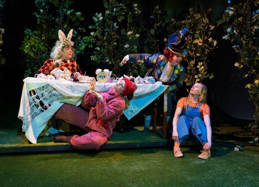 Teekutsut on katettu liinalla peitetylle pöydälle puutarhamaisessa ympäristössä pensaiden keskellä. Liisa istuu pöydän vieressä maassa ja katsoo seuruetta pöydän ääressä. Pöydän ääressä istuvat Hattumaakari ja Mieletön Jänis.
