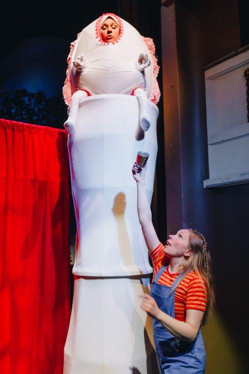 Hälläri Välläri istuu tornin nokassa. Liisa kurottelee sormustinta häntä kohti.