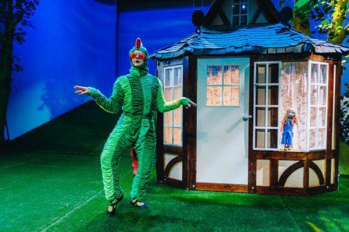 Sammakko poseeraa talon vieressä. Talon ikkunalla on pienikokoinen Liisa-nukke.