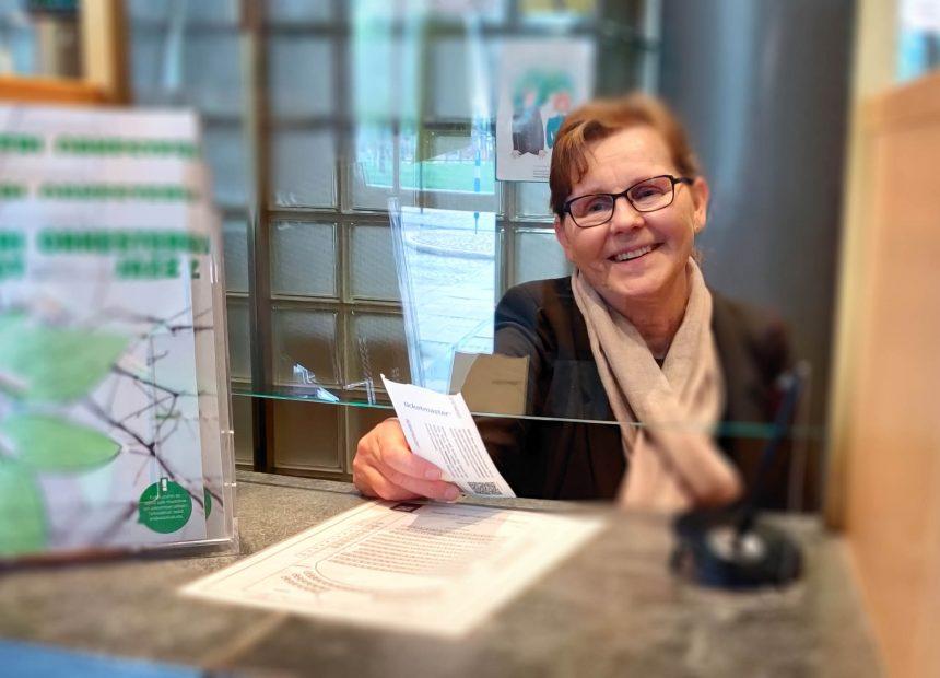 Lippukassanhoitaja Anita Auvinen ojentaa lippua teatterin ovilipunmyynnissä.