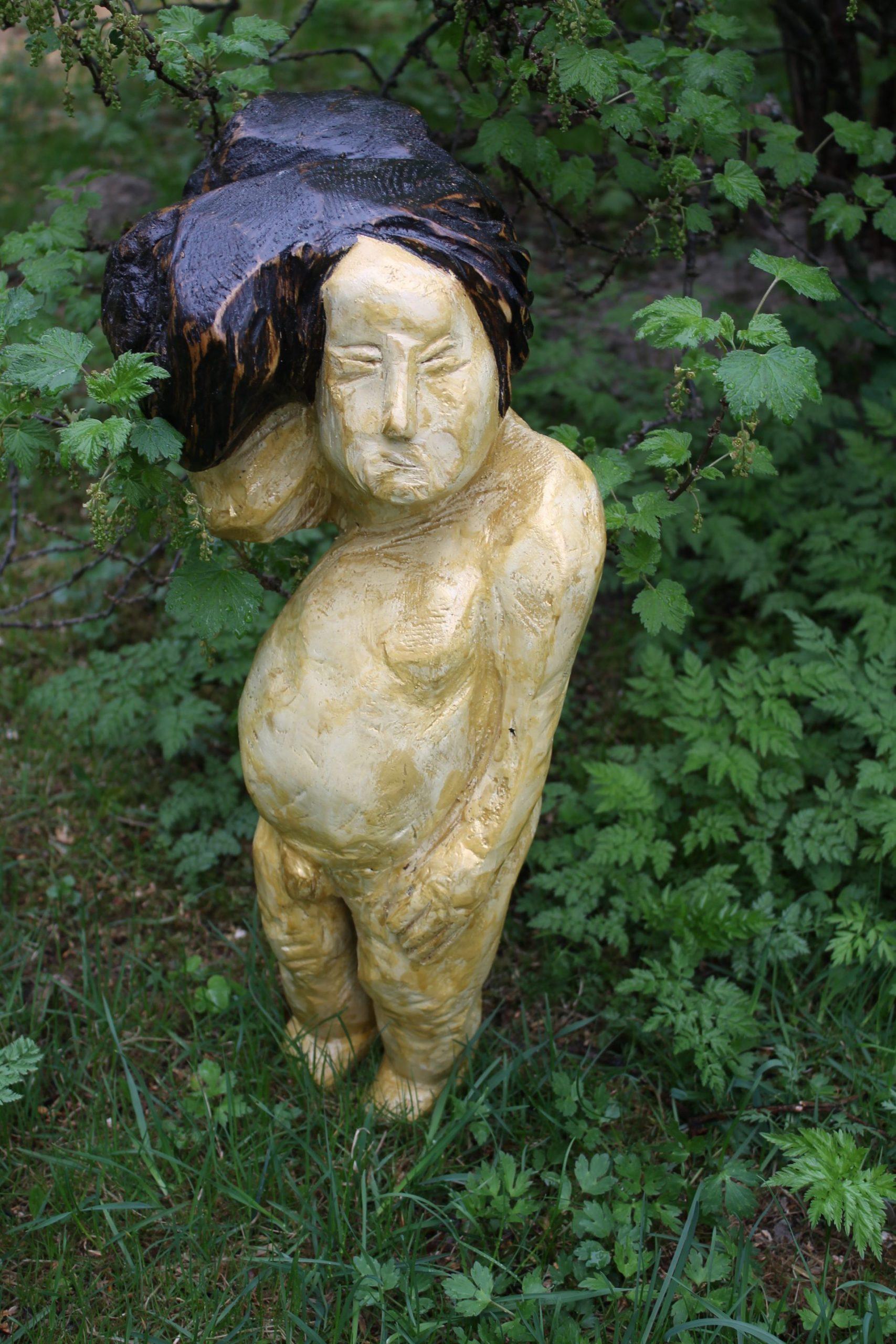 Veistos, joka esittää alastonta poikaa.