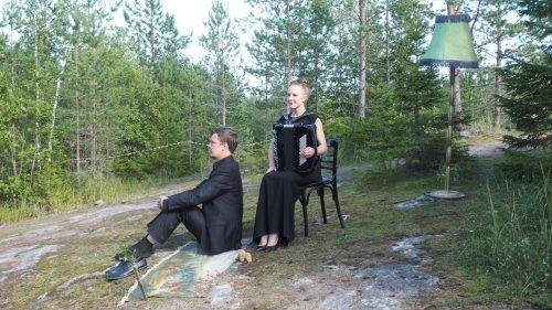 Naisnäyttelijä haitari sylissään istuu miesnäyttelijän kanssa kalliolla.
