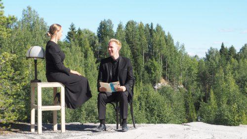 Nais- ja miesnäyttelijä istuvat kalliolla hymyillen toisilleen.