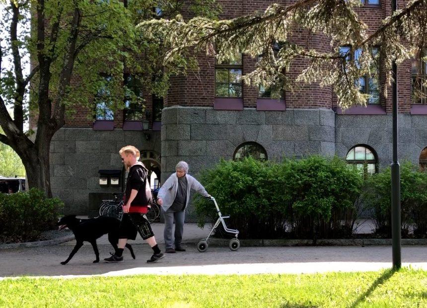 Aimo Kätkäläinen (Regina Launivuo) seisoo kadulla rollaattoriin nojaten ja ojentaa kättään kohti vastaan tulevaa nuoren miehen taluttamaa mustaa koiraa.