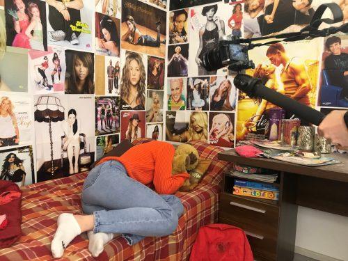Nuori Solveig (Anni Turunen) makaa kippurassa sängyllä, jota ympäröivät seinät on peitetty julisteilla.