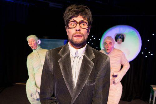Mies puvuntakki päällä (Virallinen henkilö) seisoo etualalla kauhistuneen näköisenä. Hänellä on tuuhea ruskea tukka ja isot kulmikkaat silmälasit. Hänen takaansa kurkistaa kaksi avaruusoliota (Pim ja Pam), yksi kummaltakin puolelta, uteliaan ja yllättyneen näköisinä.