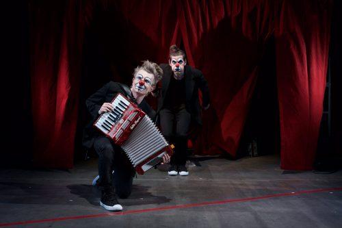Klovnineniin ja tummiin pukuihin sonnustautuneet miehet poseeraavat teatterin punaisen esiripun edessä. Toinen soittaa harmonikkaa.