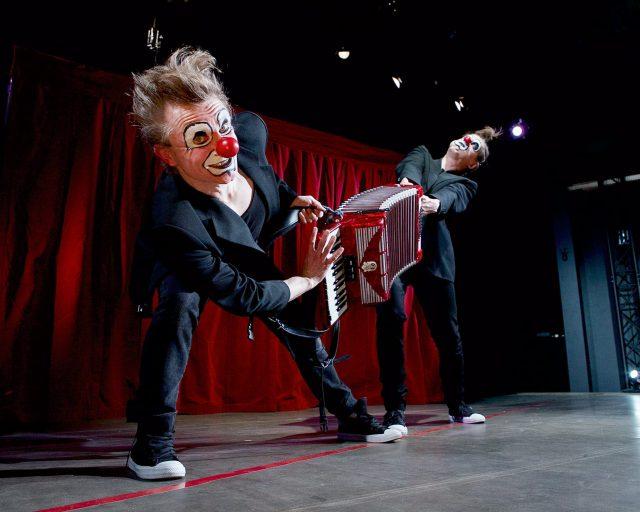 Klovninenäiset, tummiin pukuihin pukeutuneet miehet soittavat harmonikkaa eri päistä.