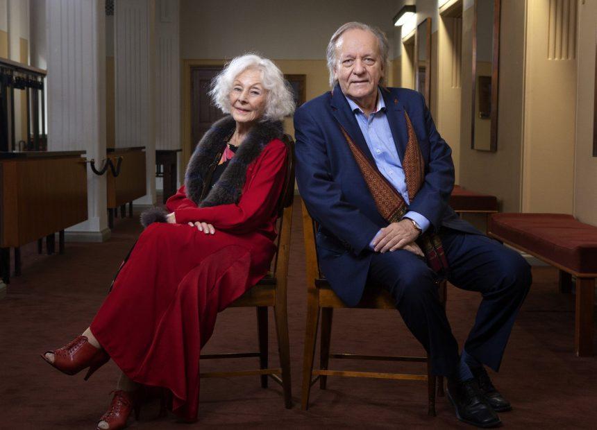 Varttuneet nainen ja mies istuvat puisilla tuoleilla vinosti selät vastakkain ja kääntyneinä kameraa kohti. Heillä on yllään juhlavat asut: naisella tulipunainen pitkä mekko ja miehellä tummansininen puku.
