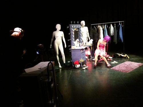 Pinkkihiuksinen Solveig (Tiia-Mari Mäkinen) istuu spottivaloissa lavasteissa ympärillään mallinukkeja ja vaaterekki.