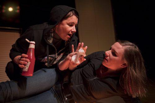 Hukka (Anna Ojanne) kumartuu ketsuppipullo kädessään kohti väistävää Annaa (Minni Gråhn).