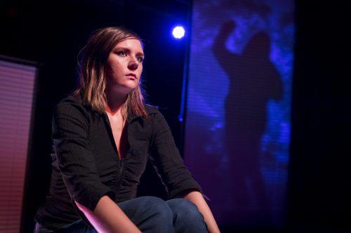 Anna (Minni Gråhn) istuu etualalla. Taustalla sinistä seinää vasten näkyy ihmishahmoinen varjokuva.