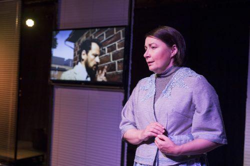 Sofia (Anna Ojanne) seisoo etualalla. Taustalla näkyy ruudulla videokuvassa Richard (Hans Stigzelius).
