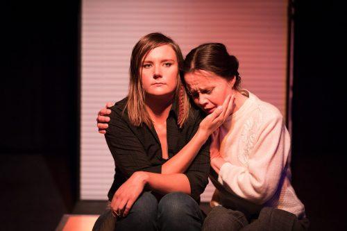 Anna (Minni Gråhn) ja Katariina (Maria Karhapää) istuvat toisiinsa nojaten, Anna pitää kättään surevan Katariinan poskella.