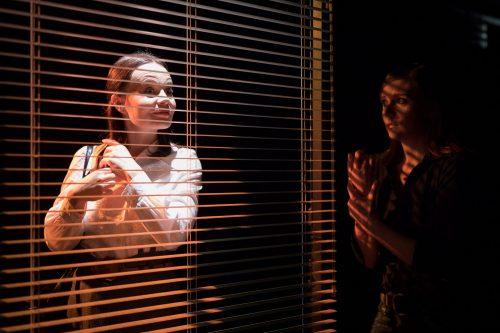 Katariina (Maria Karhapää) katsoo kirkkaassa valossa sälekaihtimien takaa. Anna (Minni Gråhn) katsoo häntä varjoista sivulta.