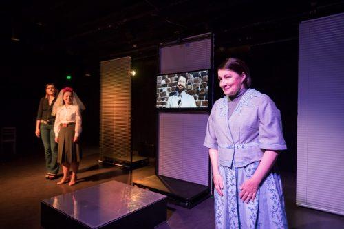 Sofia (Anna Ojanne) etualalla. Taustalla television ruudulla näkyy Richard (Hans Stigzelius). Anna (Minni Gråhn) ja Katariina (Maria Karhapää) seisovat taustalla.