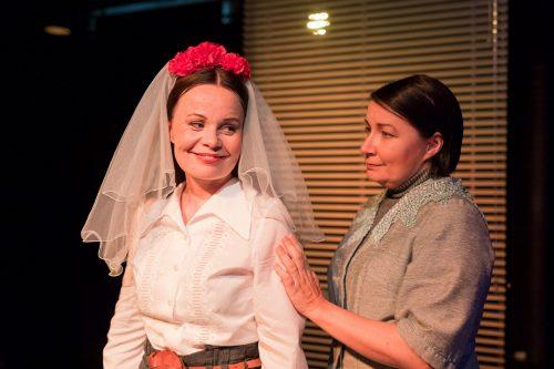 Katariina (Maria Karhapää) huntu päässään. Sofia (Anna Ojanne) on vieressä, käsi kevyesti Katariinan olkavarrella. He hymyilevät.