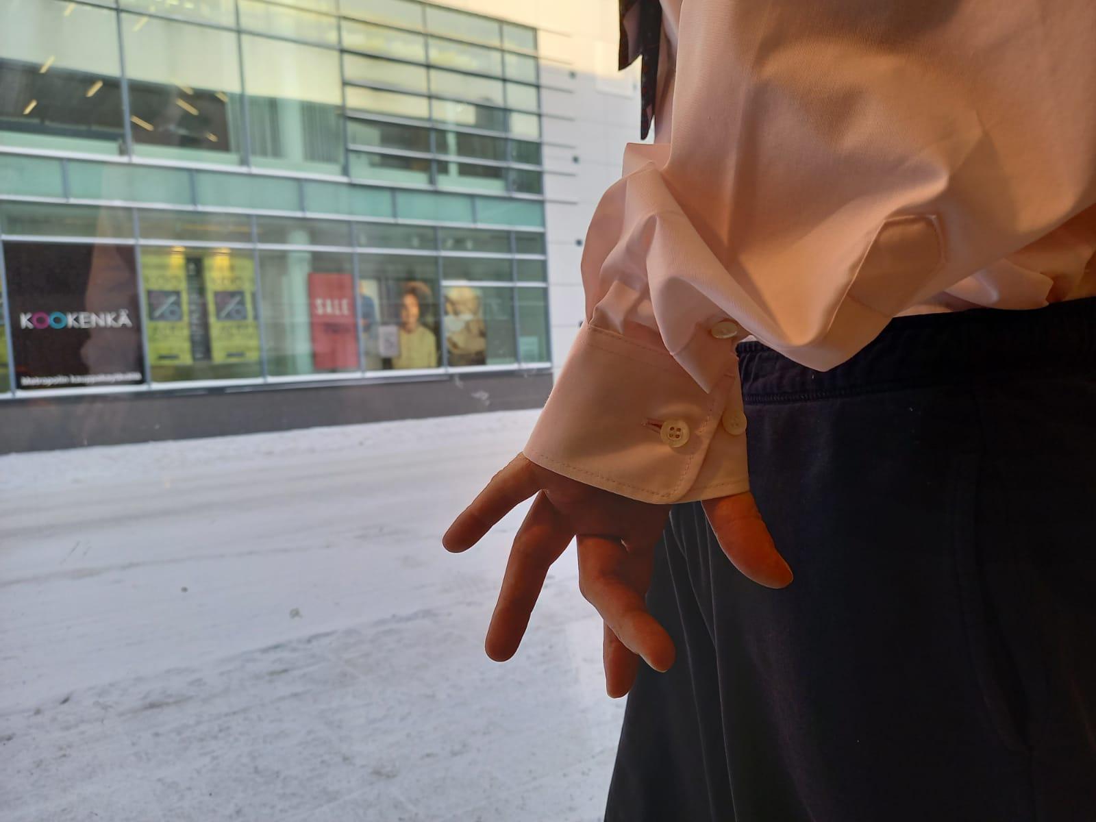 Kauluspaitaan ja puvun housuihin pukeutunut henkilö näyteikkunan edessä kuvattuna niin, että vain käden ojennetut sormet ja osa kehoa näkyy.